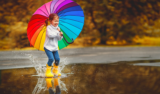 Happy funny child girl with  umbrella jumping on puddles in rubber boots