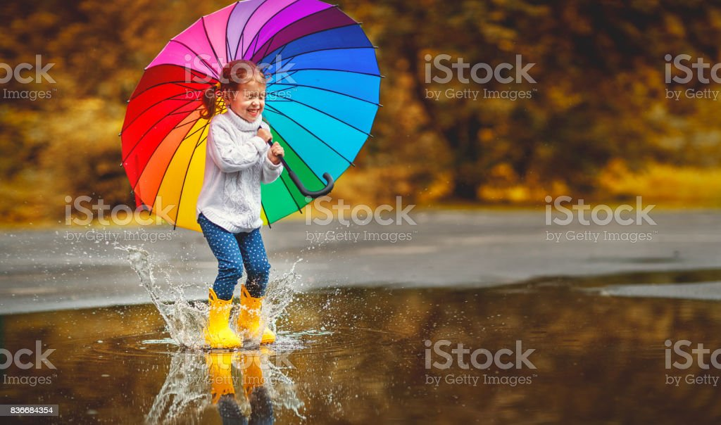 Happy funny child girl with  umbrella jumping on puddles in rubber boots stock photo