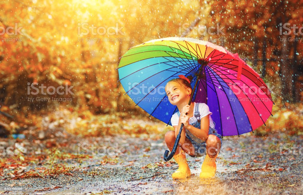 Menina criança engraçada feliz com guarda-chuva pular em poças de botas de borracha - foto de acervo