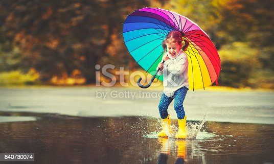 istock Happy funny child girl with  umbrella jumping on puddles in rubber boots 840730074