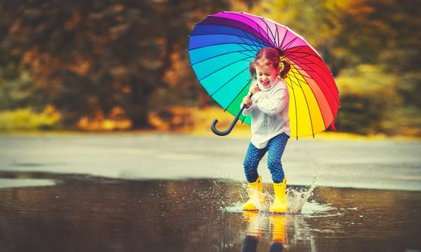fille enfant drôle heureux avec parapluie, sauter sur les flaques d'eau dans les bottes en caoutchouc - sauter photos et images de collection