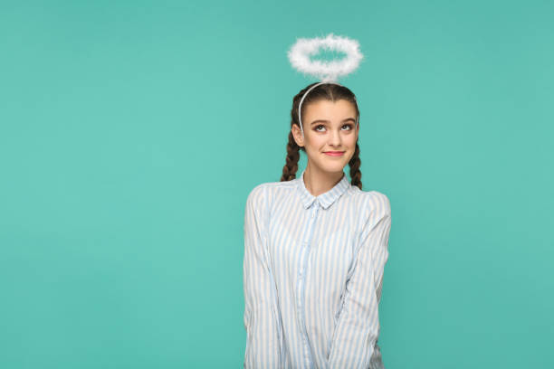 Happy funny girl in striped blue shirt and pigtail hairstyle, standing with halo on her head and looking away with smile and dreaming face stock photo