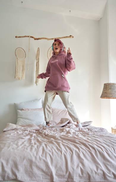 ピンクの髪を持つ幸せな面白いヒップスターの十代の少女は、ラジオポップミュージックプレイリストポッドキャストを聴いてパーカーとヘッドフォンを着用し、居心地の良いヒュッゲの寝� - gen z ストックフォトと画像