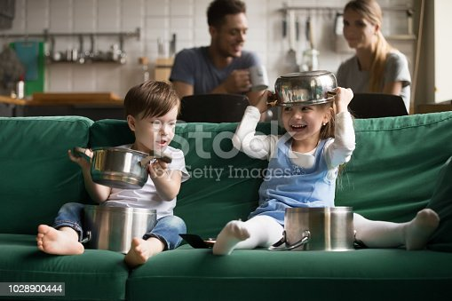 505657693 istock photo Happy funny kids playing with kitchenware cooking pots at home 1028900444