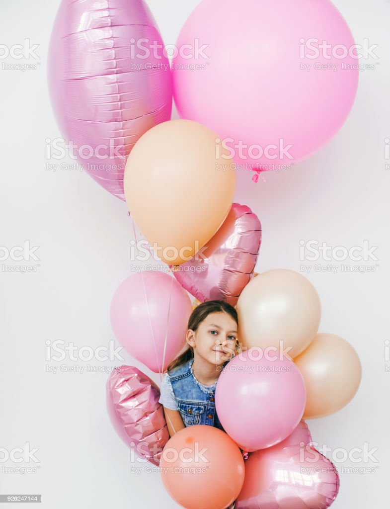 Happy funny little girl with balloons studio shot stock photo