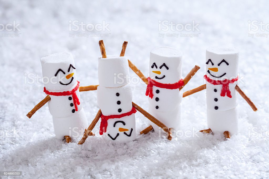 Happy funny marshmallow snowmans on snow stock photo