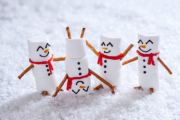 happy funny marshmallow snowmans on snow - lustige grußkarten stock-fotos und bilder