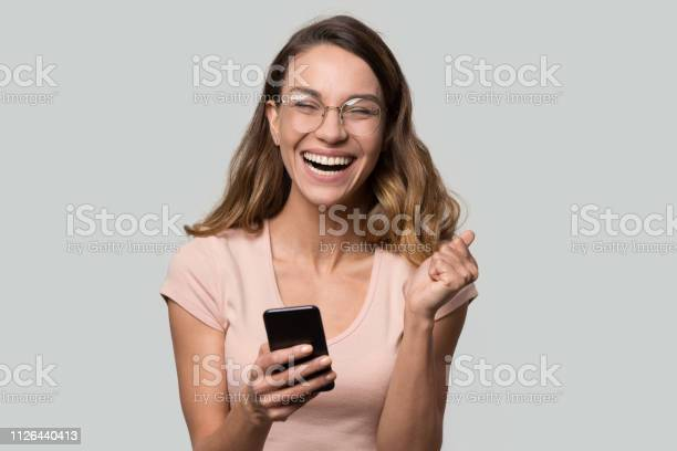 Happy funny millennial woman celebrating mobile win isolated on picture id1126440413?b=1&k=6&m=1126440413&s=612x612&h=mlowfopje5wqag883yrihgac9kxyokmukqvwiuafoco=