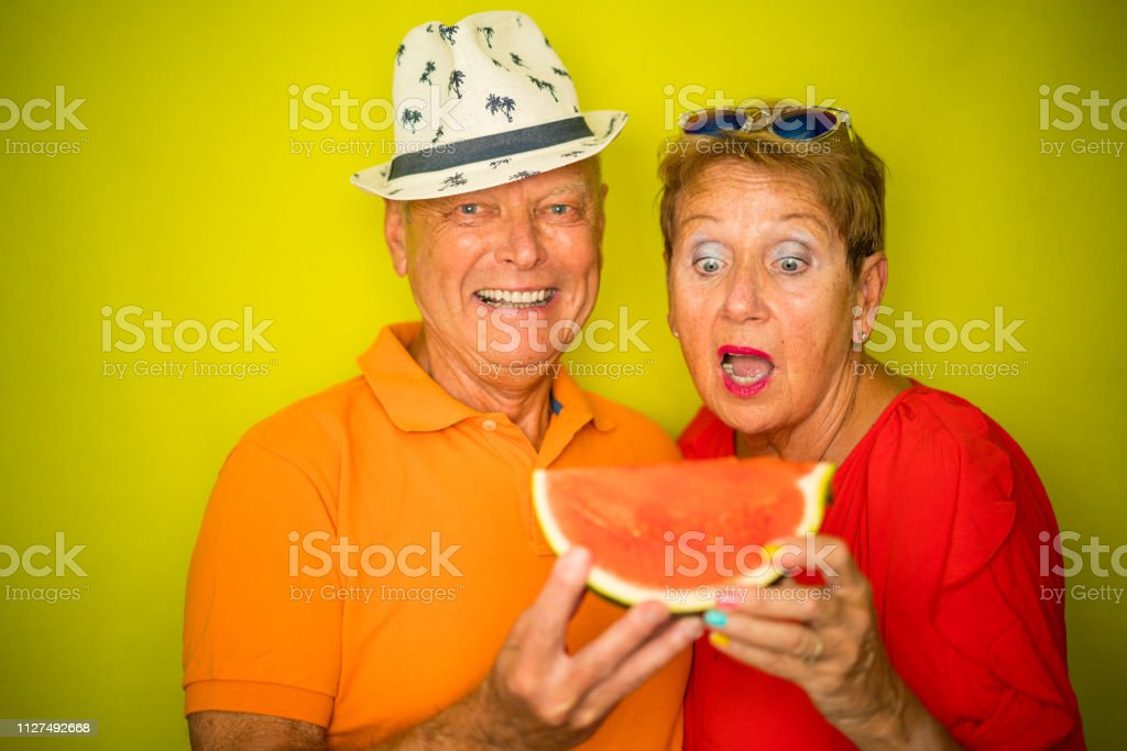 cool senior 70 year old couple eating water melon together, showing...