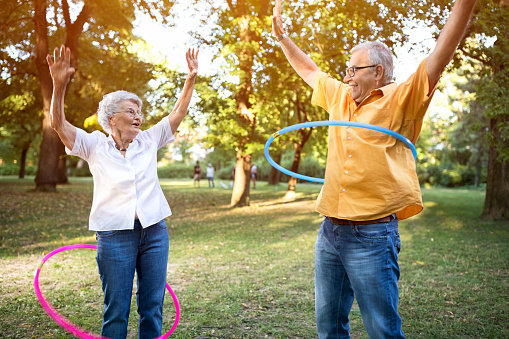 istock Happy funny senior couple playing hulahop in park 613759740