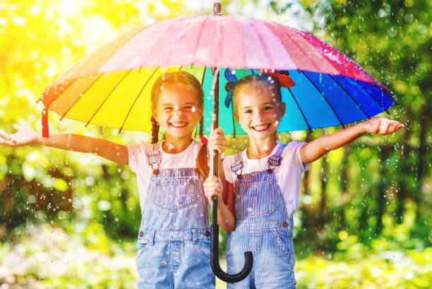glücklich lustig schwestern zwillinge kind mädchen mit regenschirm - mädchen dusche stock-fotos und bilder