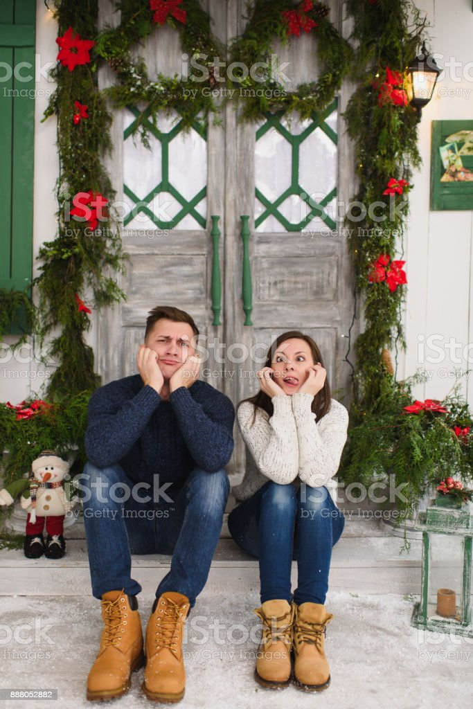 Happy funny young couple in love dressed in sweater sitting on porch...