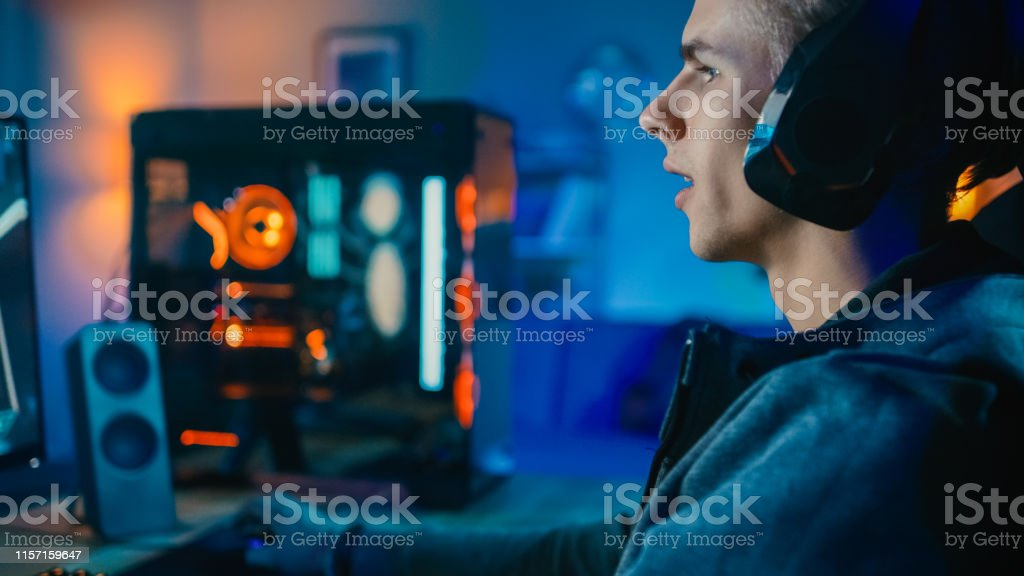 Happy Gamer in Headset with a Mic Playing Shooter Online Video Game...