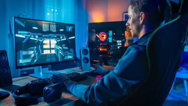 Happy Gamer spielen First-Person Shooter Online-Videospiel auf seinem leistungsstarken Personal Computer. Zimmer und PC haben bunte Neon Led Lights. Gemütlicher Abend zu Hause. – Foto