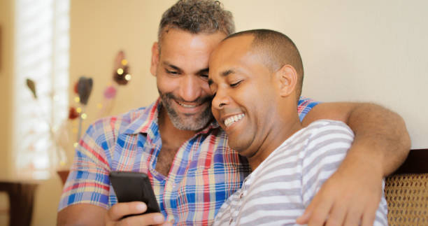 Happy Gay Couple Looking At Pictures On Mobile Phone Homosexual couple, gay hispanic men watching media on mobile phone, sitting on sofa at home. gay man stock pictures, royalty-free photos & images