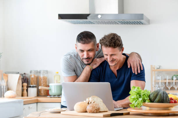 Happy gay male couple using internet together at home Happy gay male couple using internet having a good time together in kitchen at home gay couple stock pictures, royalty-free photos & images