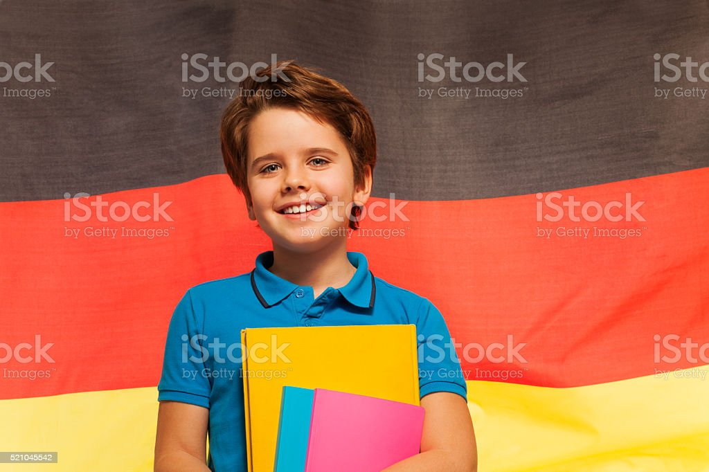 Happy German schoolboy with textbooks in his hand stock photo