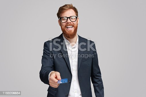 istock Happy ginger businessman giving bank card 1153206654