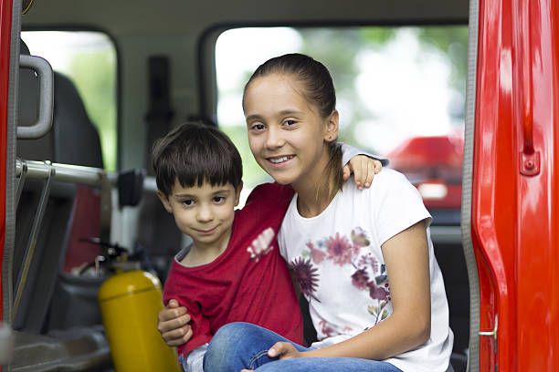 Happy Girl and Boy in Firefighter Car stock photo