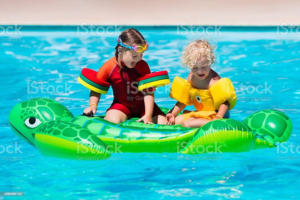 Happy girl and boy in swimming pool with inflatable toy stock photo