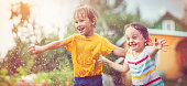 Sister and brother jumping through spray at back yard in summer
