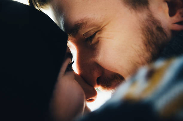 Happy girl and guy kissing and touches noses with each other. stock photo