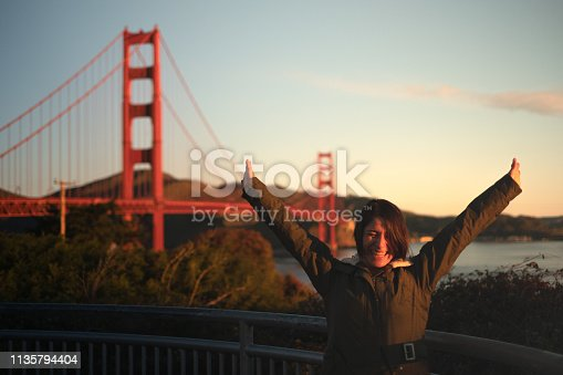 portait of happy girl arms wide open at Golden gate bridge in San Francisco