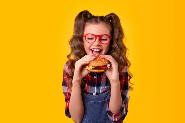 Happy girl biting delicious hamburger stock photo