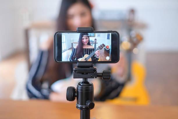 Glückliche Mädchen Blogger in Café Live-Gitarre auf Sendungen Website für Zuschauer zu sehen, Blogger Konzept