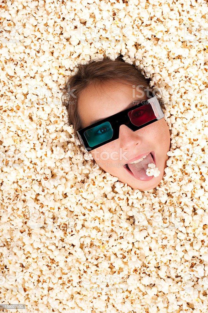 Happy girl burying herself in popcorn royalty-free stock photo