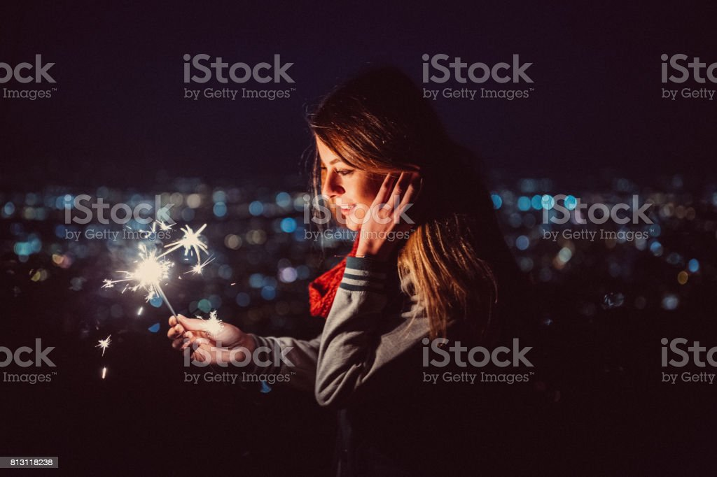 Happy girl by night holding burning sparklers stock photo