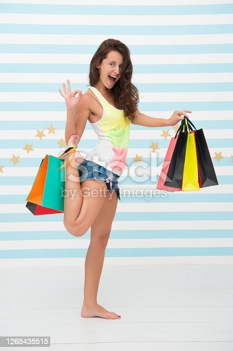 happy girl carries shopping bags. best discounts and promo codes. happy girl go shopping on black friday sale. excited shopper showing ok gesture. successful purshase