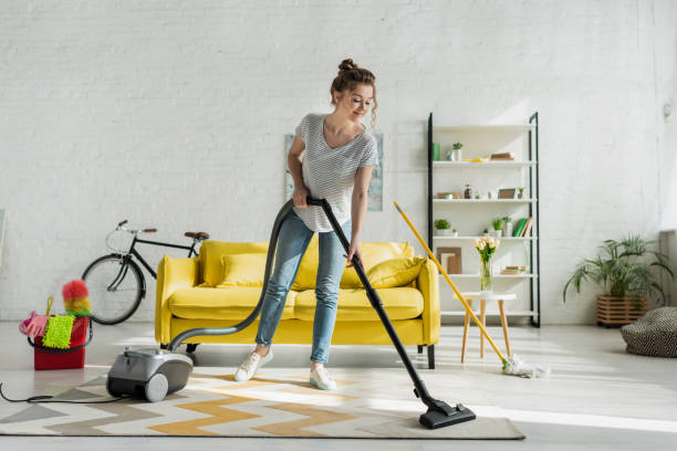 happy girl cleaning carpet with vacuum cleaner stock photo