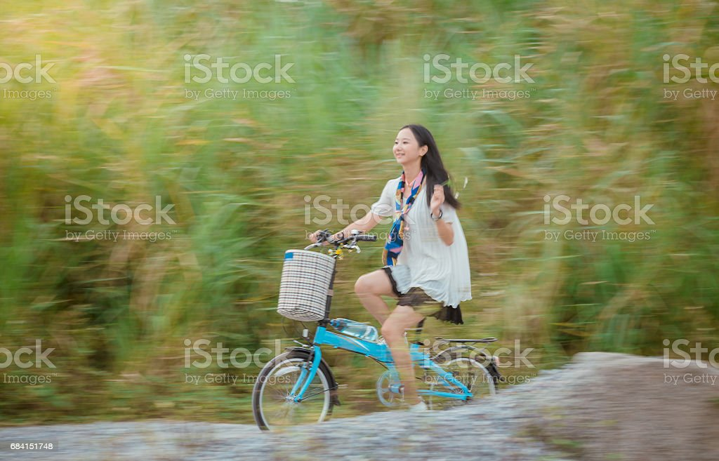Happy Girl Cycling A Bike In The Field royalty free stockfoto