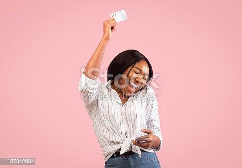 861940002 istock photo Happy Girl Dancing Holding Phone And Credit Card, Studio Shot 1187342834