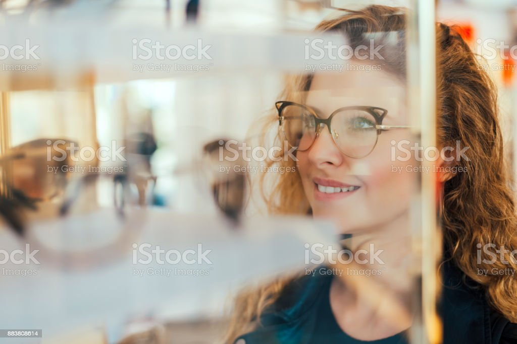 Happy girl deciding to buy new glasses. royalty-free stock photo