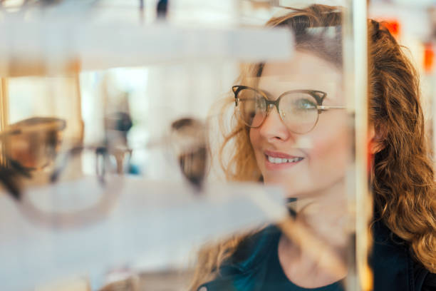 happy girl deciding to buy new glasses. - optometrist stock pictures, royalty-free photos & images
