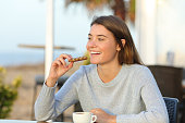 istock Happy girl eating a snack in a cafe terrace 1208293009