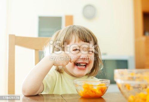 176993221istockphoto Happy  girl eating carrot salad 178425175