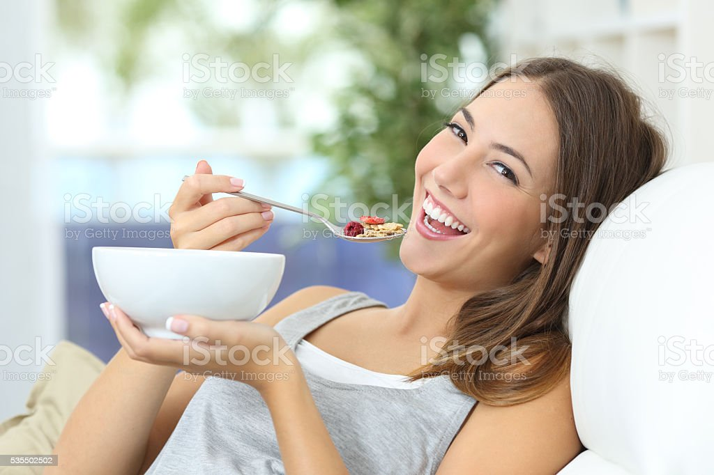 Happy girl eating cereals at home stock photo