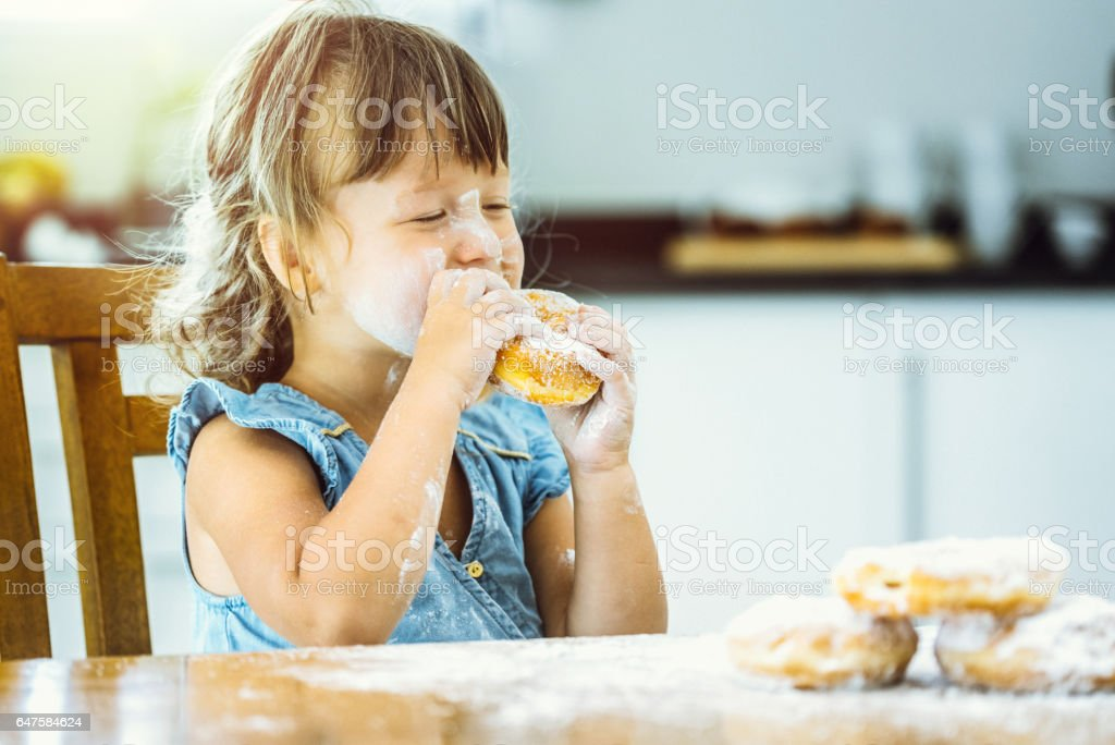 Happy girl eating delicious donut stock photo