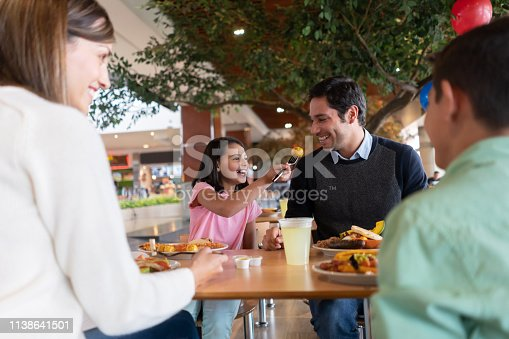 Happy girl eating luch with her family and sharing food with her father while smiling - lifestyle concepts