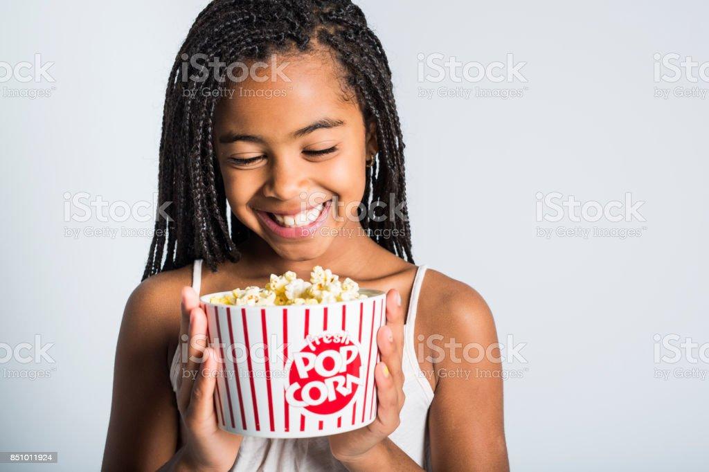 happy girl eating popcorn over gray background stock photo