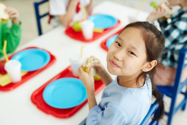 Happy girl eating school lunch Pretty Asian girl sitting at table with classmates in primary school canteen, eating sandwich and smiling at camera cheerfully hungry child stock pictures, royalty-free photos & images
