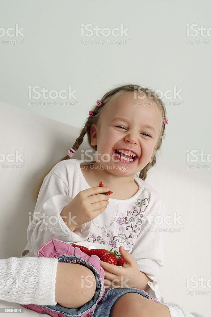 Happy girl eating strawberry royalty-free stock photo