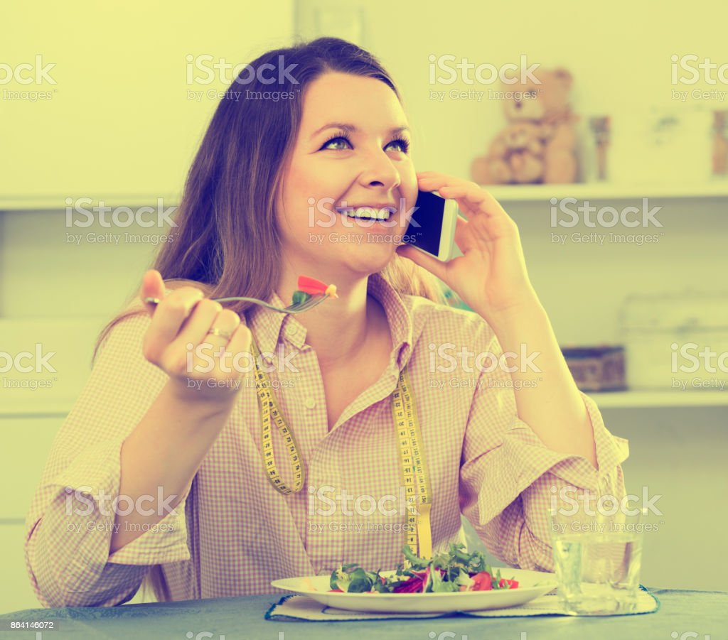 Happy girl eating tasty green salad and using smartphone royalty-free stock photo