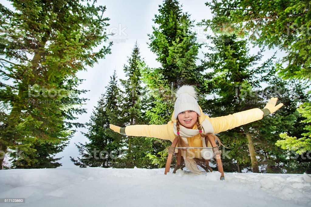 Happy girl enjoying a sledge ride in the forest stock photo