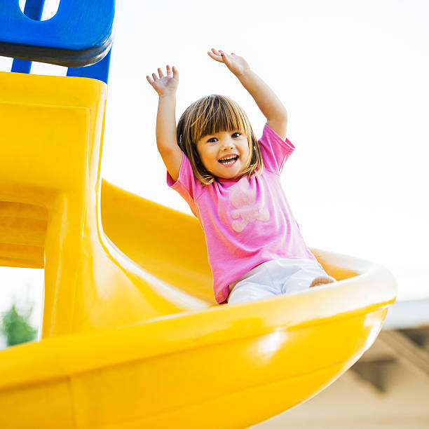happy girl enjoying in the playground. - sliding stock photos and pictures
