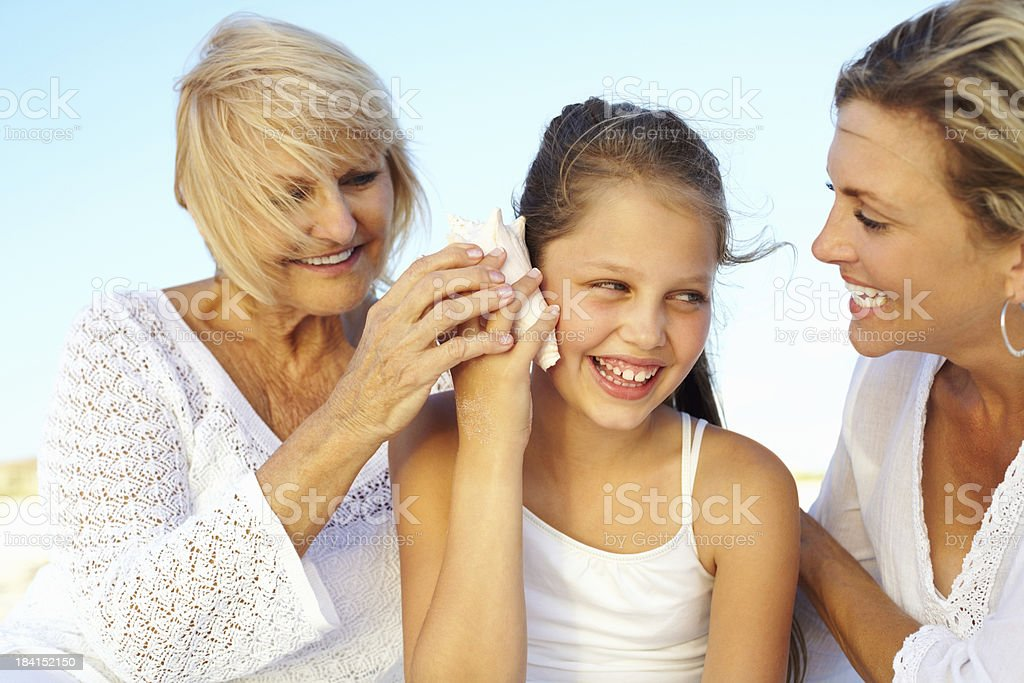 Happy girl enjoying seashell music with grandmother and mother royalty-free stock photo
