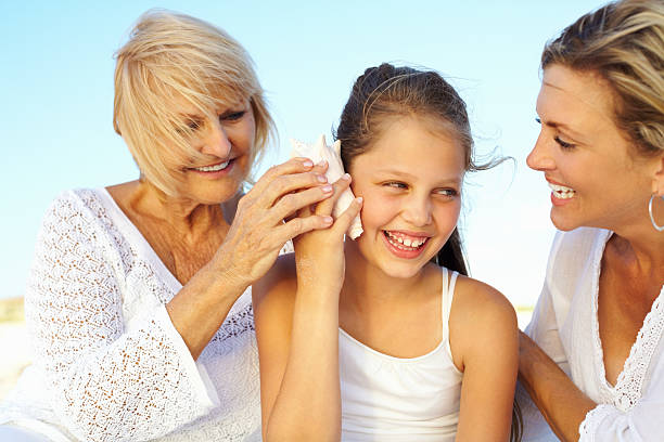 Happy girl enjoying seashell music with grandmother and mother stock photo